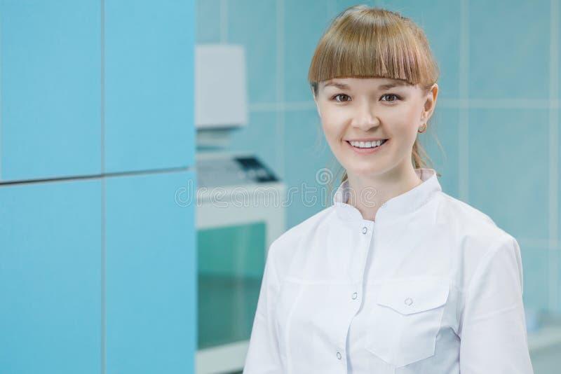 Усмехаясь женский ассистент дантиста на приеме в современном зубоврачебном офисе клиники стоковое фото rf
