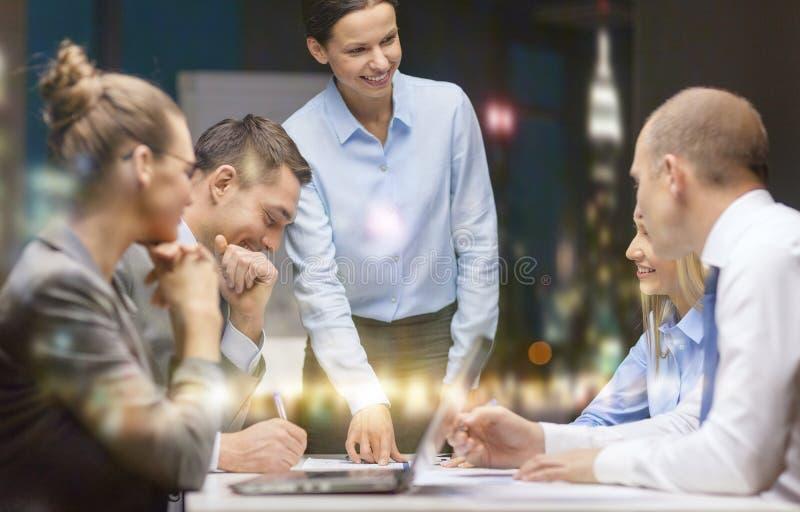 Усмехаясь женский босс говоря к команде дела стоковое фото rf