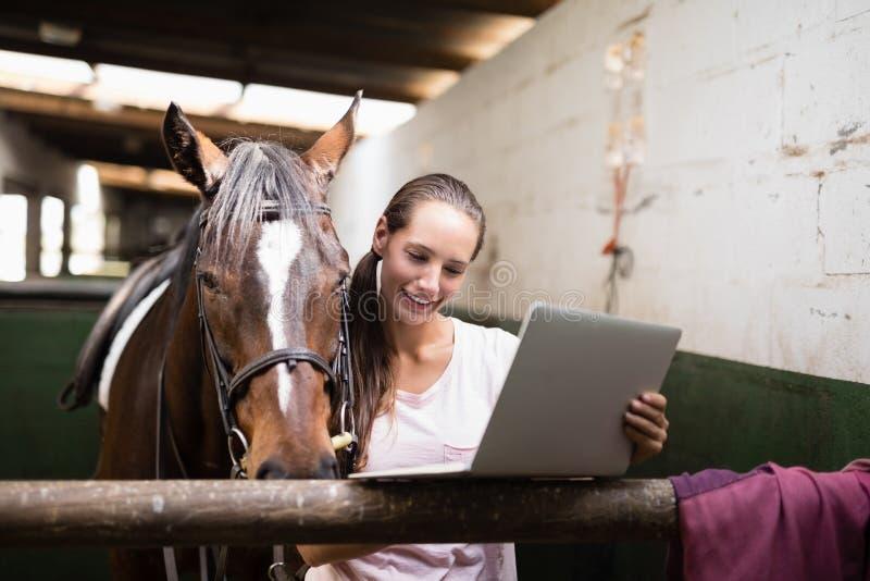 Усмехаясь женский жокей используя компьтер-книжку пока готовящ лошадь стоковое фото