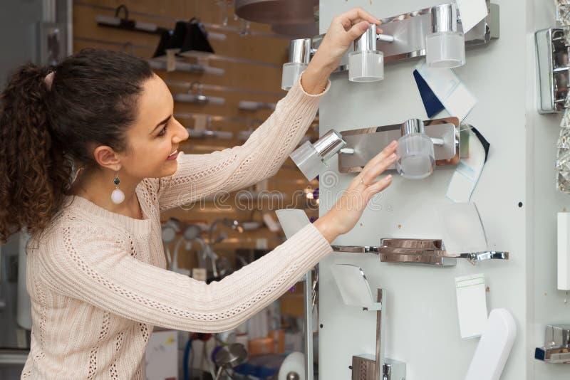 Усмехаясь женский клиент покупая внутренние света для дома стоковое фото