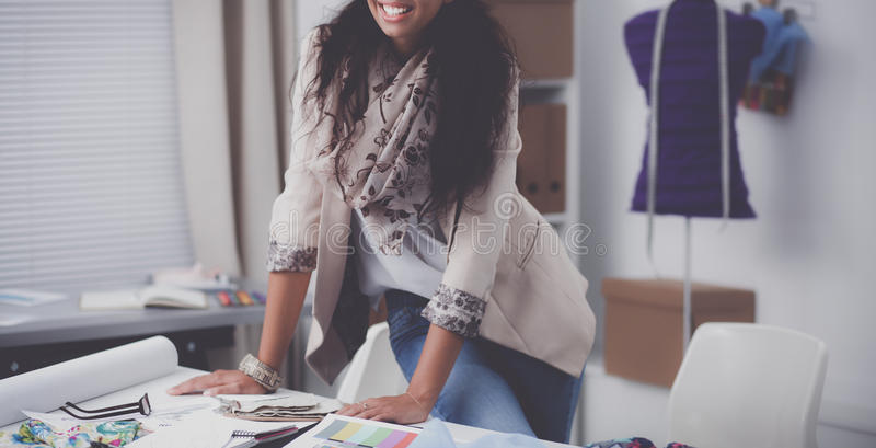 Усмехаясь женский модельер сидя на столе офиса стоковые фото