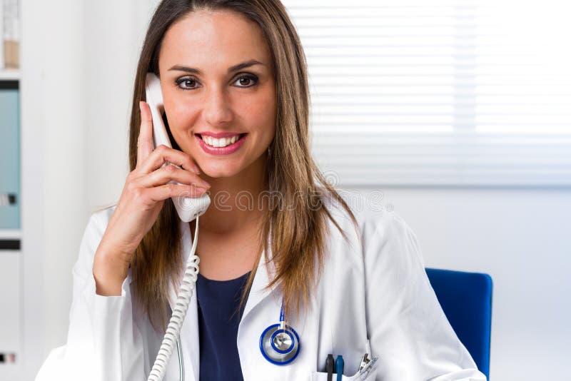 Усмехаясь женский доктор с телефоном к уху стоковые фотографии rf