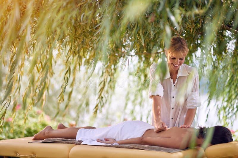 Усмехаясь женский получая задний массаж от professiona массажа стоковые изображения rf
