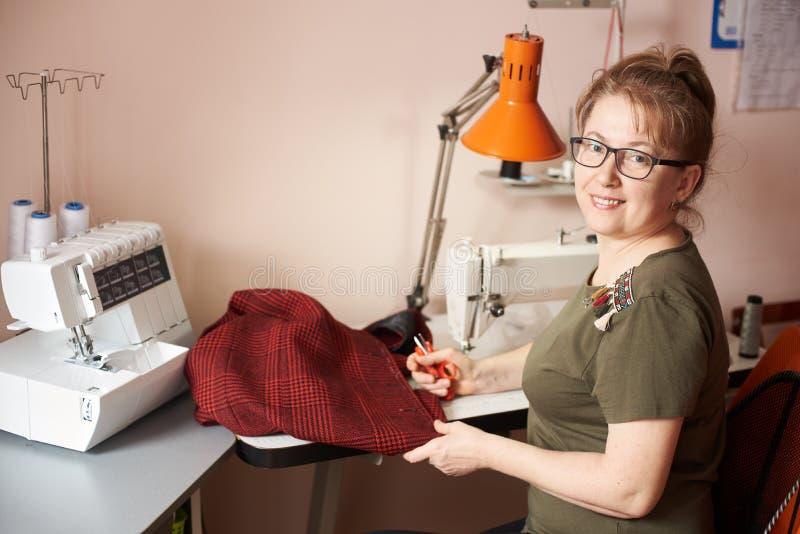 Усмехаясь женский портной на шить процессе юбки, держа ножницы Overlock и шить-машина на предпосылке r стоковые изображения