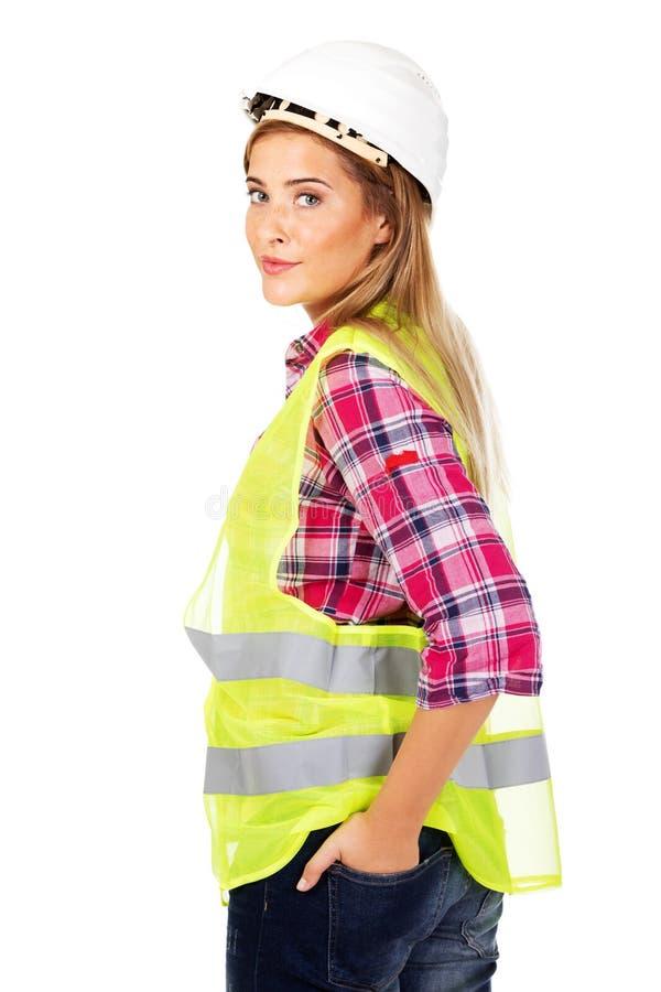 Усмехаясь женский построитель держа руки в карманн стоковые изображения rf