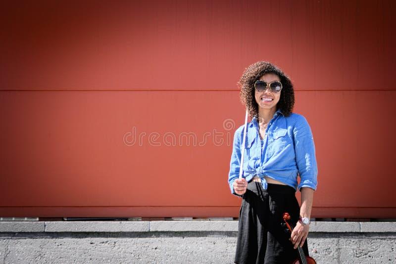 Усмехаясь женский скрипач держа аппаратуру outdoors стоковые фотографии rf