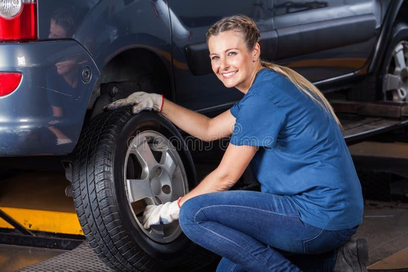 Усмехаясь женский техник регулируя автошину автомобиля стоковое фото
