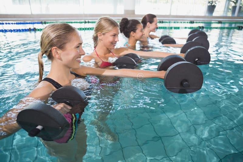 Усмехаясь женский фитнес классифицирует делать аэробику aqua с гантелями пены стоковое фото rf