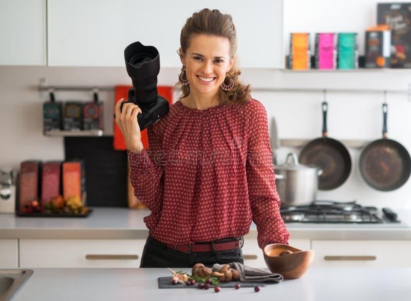 Усмехаясь женский фотограф еды в кухне стоковое фото