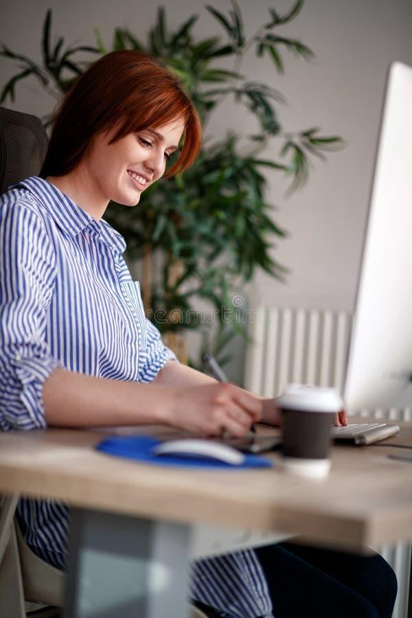 Усмехаясь женский фрилансер предпринимателя работая используя компьютер стоковое фото rf
