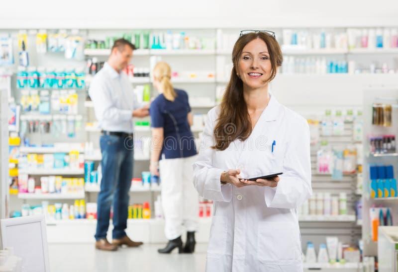 Усмехаясь женский химик держа таблетку цифров на стоковая фотография rf