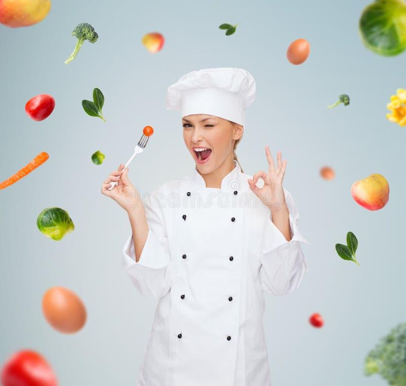 Усмехаясь женский шеф-повар с вилкой и томатом стоковая фотография rf