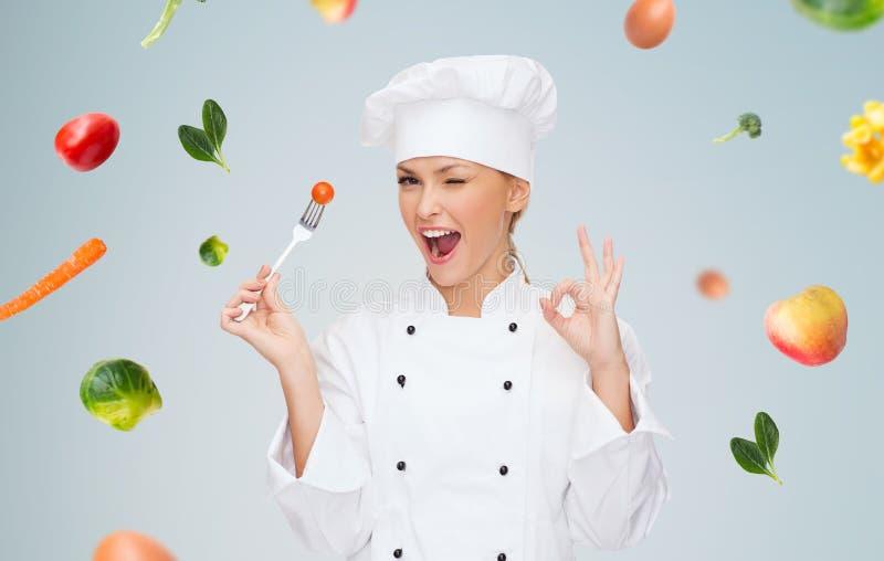 Усмехаясь женский шеф-повар с вилкой и томатом стоковое фото rf