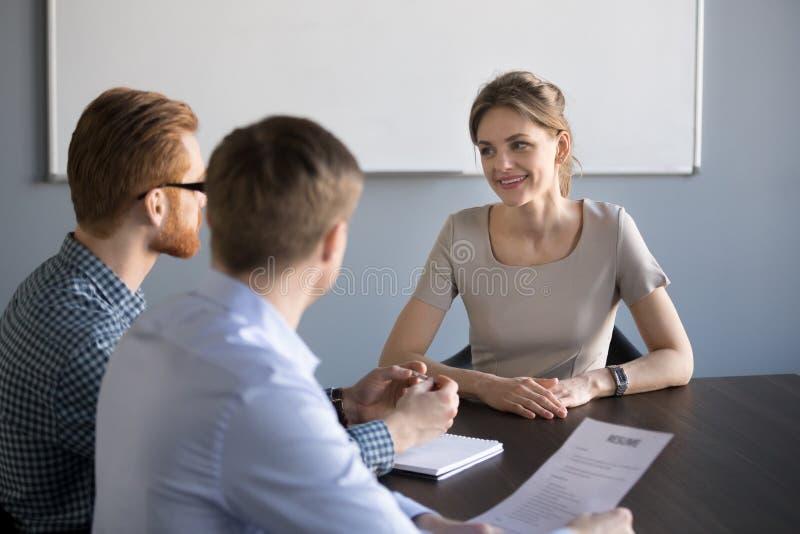 Усмехаясь женское интервью заявителя с мужскими специалистами по набору персонала в offic стоковые изображения rf