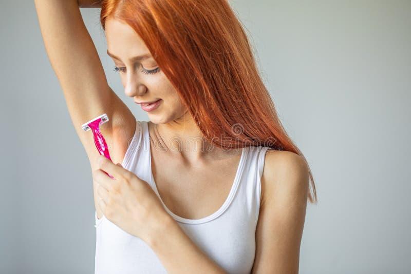 Усмехаясь женщина брея подмышку с розовым шевером стоковое фото rf