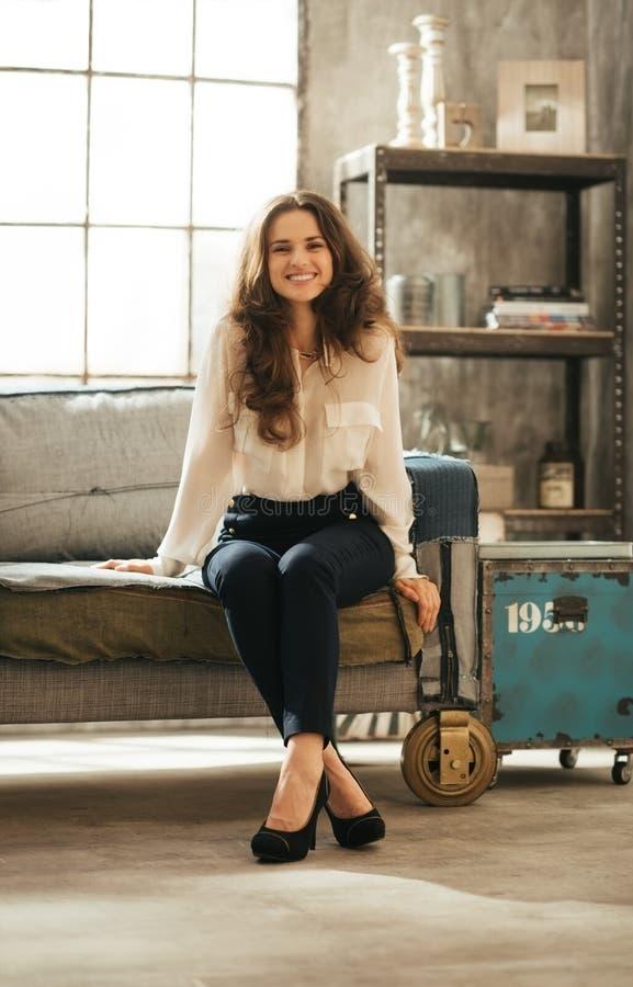 Усмехаясь женщина брюнет в элегантной одежде сидя в комнате просторной квартиры стоковое изображение