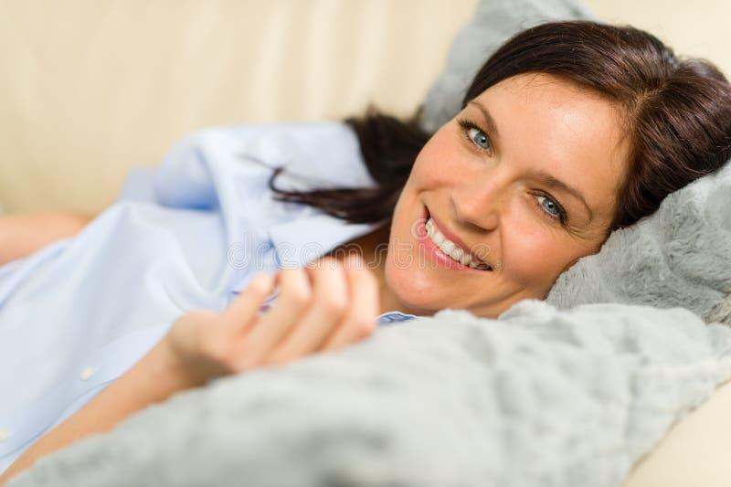 Усмехаясь женщина брюнет лежа в кровати стоковое изображение rf