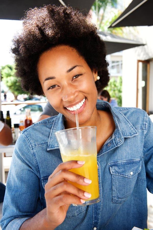 Усмехаясь женщина выпивая апельсиновый сок на кафе стоковые изображения