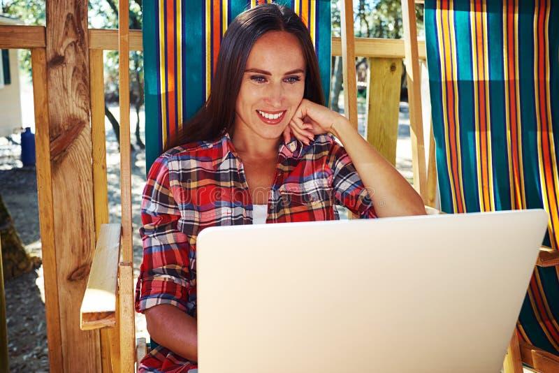 Усмехаясь женщина в вскользь обмундировании смотря экран компьтер-книжки w стоковые фото
