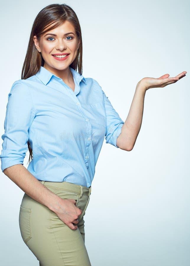 Усмехаясь женщина в голубой рубашке представляя любой продукт в наличии стоковое фото