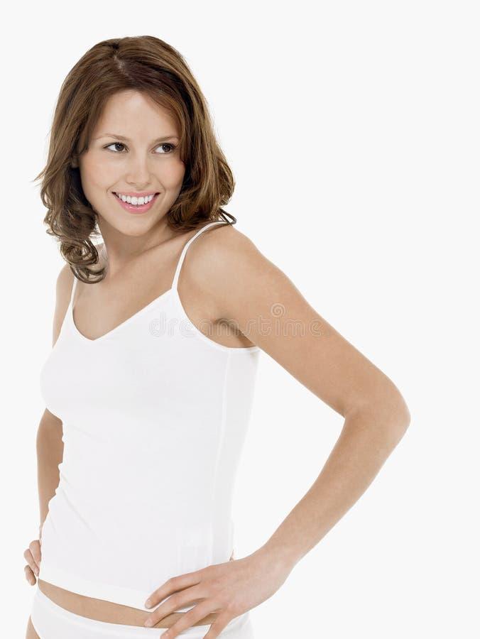 Усмехаясь женщина в лифчике с руками на бедре стоковое изображение