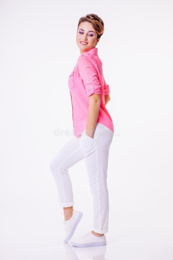 Усмехаясь женщина в розовой рубашке при короткий стиль причёсок представляя в студии и смотря вниз Экземпляр-космос стоковые фотографии rf