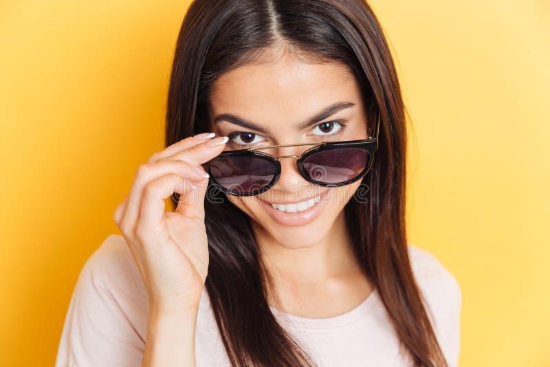 Усмехаясь женщина в солнечных очках смотря камеру стоковые фото