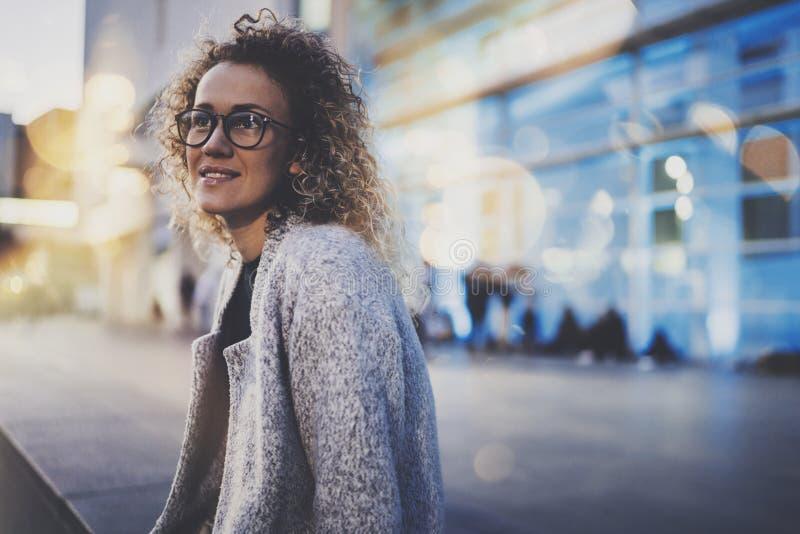 Усмехаясь женщина в стеклах глаза стильной одежды нося снаружи в европейском городе ночи Bokeh и влияние пирофакелов дальше стоковые фото