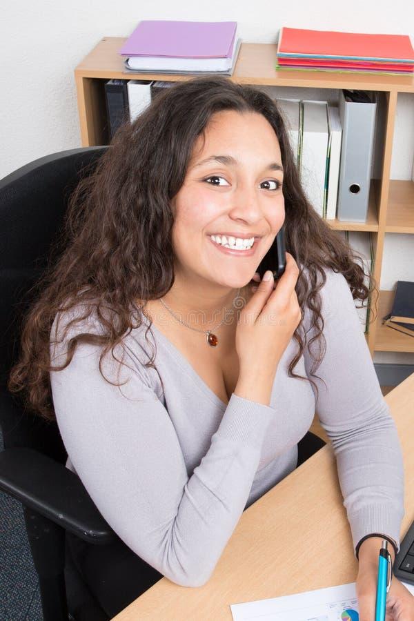 Усмехаясь женщина в телефоне на столе офиса стоковые фото