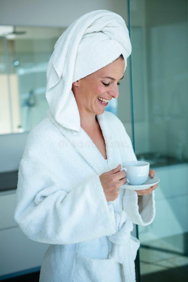 усмехаясь женщина в халате держа чашку и поддонник стоковая фотография