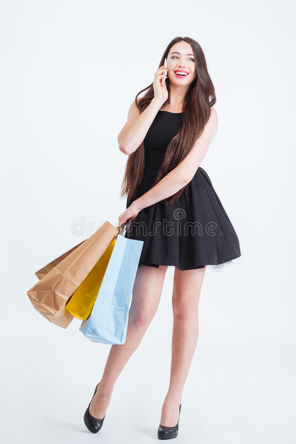 Усмехаясь женщина говоря на мобильном телефоне и держать хозяйственные сумки стоковые изображения rf