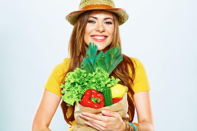 Усмехаясь женщина держа бумажную сумку с зеленой едой vegan стоковая фотография