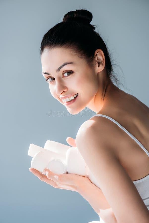 Усмехаясь женщина держа косметические контейнеры стоковое изображение