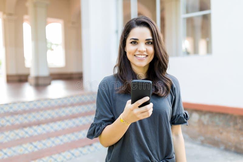 Усмехаясь женщина держа Smartphone пока стоящ против строить стоковое изображение