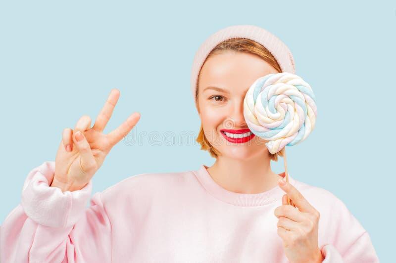 Усмехаясь женщина держит леденец на палочке конфеты на пастельной голубой предпосылке стоковые изображения rf