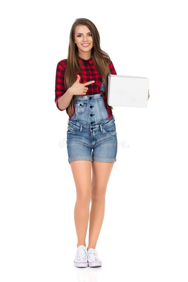 Усмехаясь женщина держа белую коробку и указывать стоковое изображение