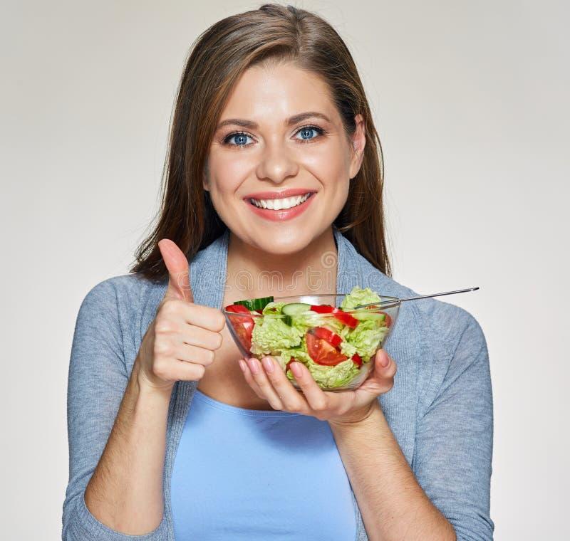 Усмехаясь женщина держа блюдо салата показывает большой палец руки вверх стоковые изображения rf