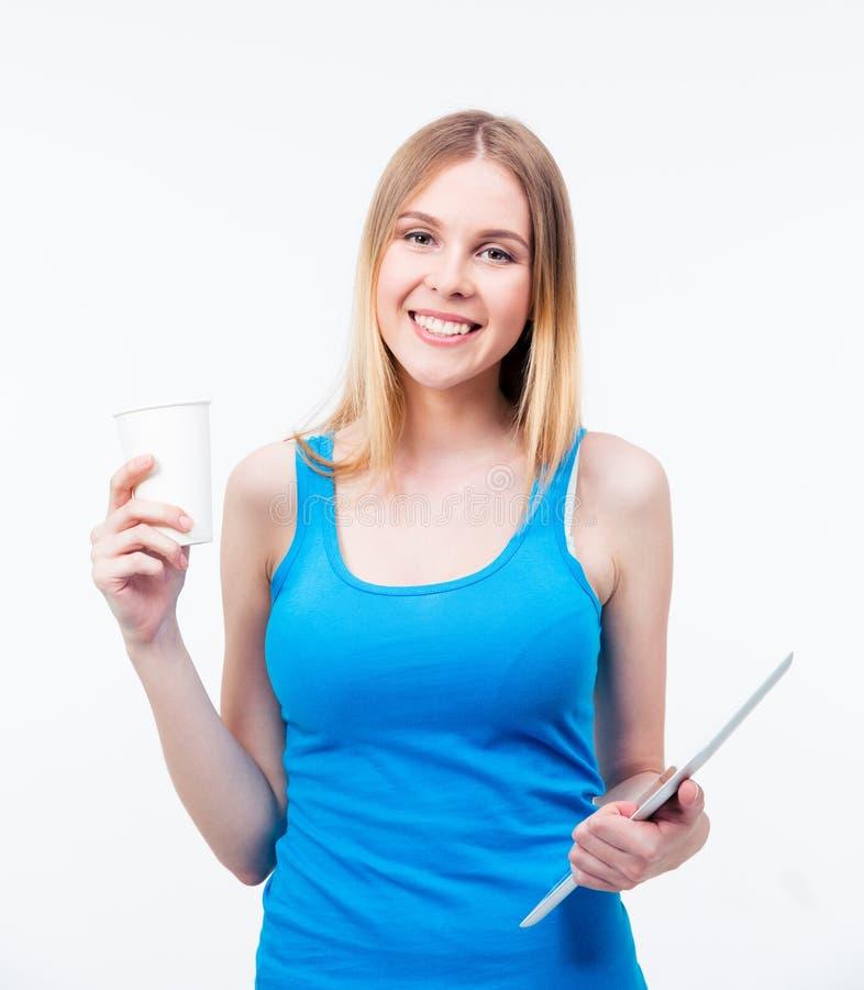 Усмехаясь женщина держа планшет и чашку с кофе стоковое изображение