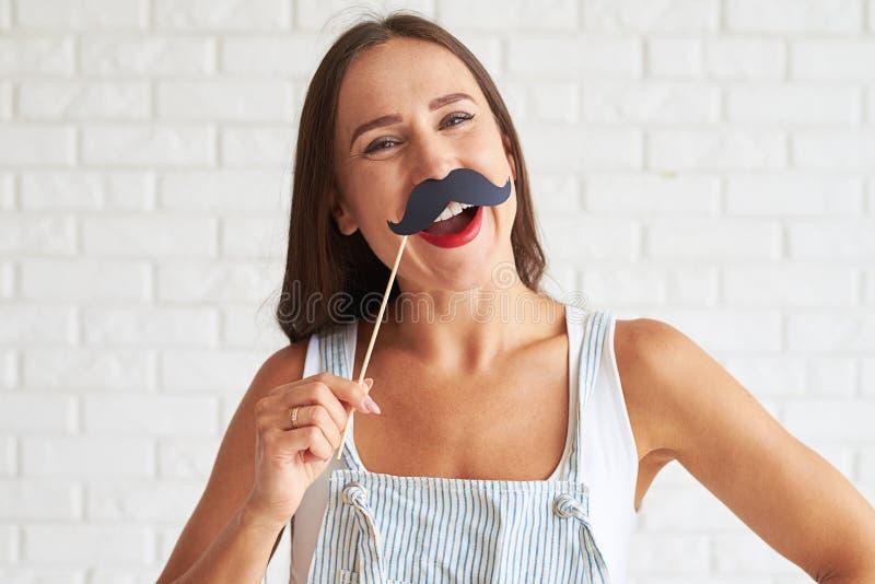 Усмехаясь женщина держа усик-маску и усмехаться стоковая фотография rf