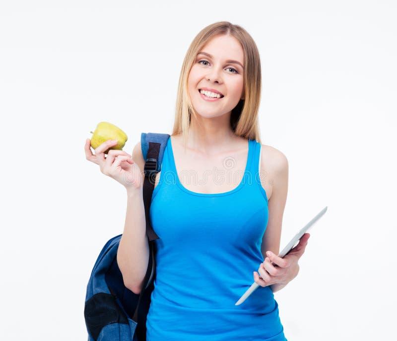Усмехаясь женщина держа яблоко и планшет стоковое изображение