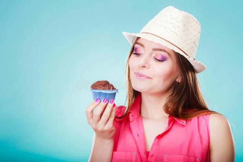 Усмехаясь женщина держит шоколадный торт в руке стоковое изображение rf