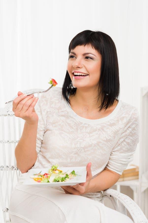 Усмехаясь женщина есть свежий салат стоковое фото