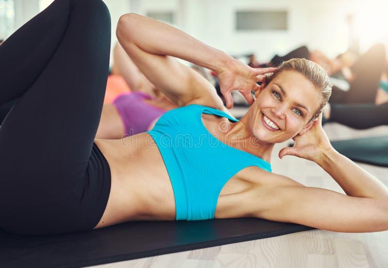 Усмехаясь женщина делая подбрюшные тренировки на циновке в спортзале стоковое изображение rf
