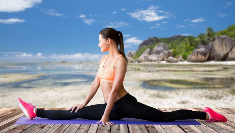 Усмехаясь женщина делая разделения на циновке над пляжем стоковое изображение rf