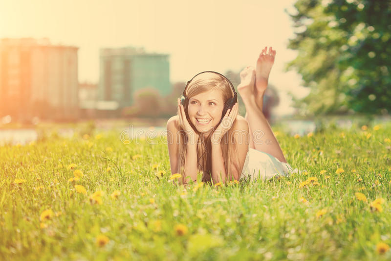 Усмехаясь женщина женщины слушая к музыке на наушниках outdoors стоковое фото rf