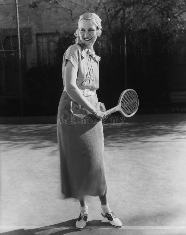 Усмехаясь женщина играя теннис (все показанные люди более длинные живущие и никакое имущество не существует Гарантии поставщика ч стоковые изображения rf