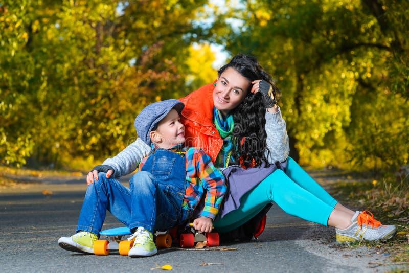 Усмехаясь женщина и мальчик сидя на пластмассе цвета стоковые изображения