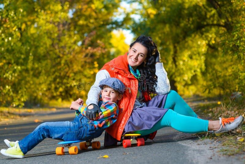 Усмехаясь женщина и мальчик сидя на пластмассе цвета стоковое фото
