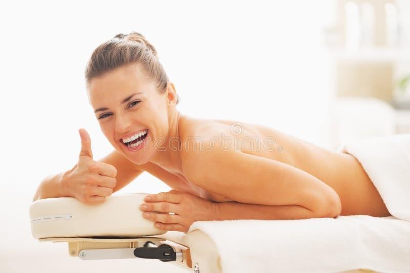 Усмехаясь женщина кладя на массаж ставит на обсуждение и показывая большие пальцы руки вверх стоковые фото