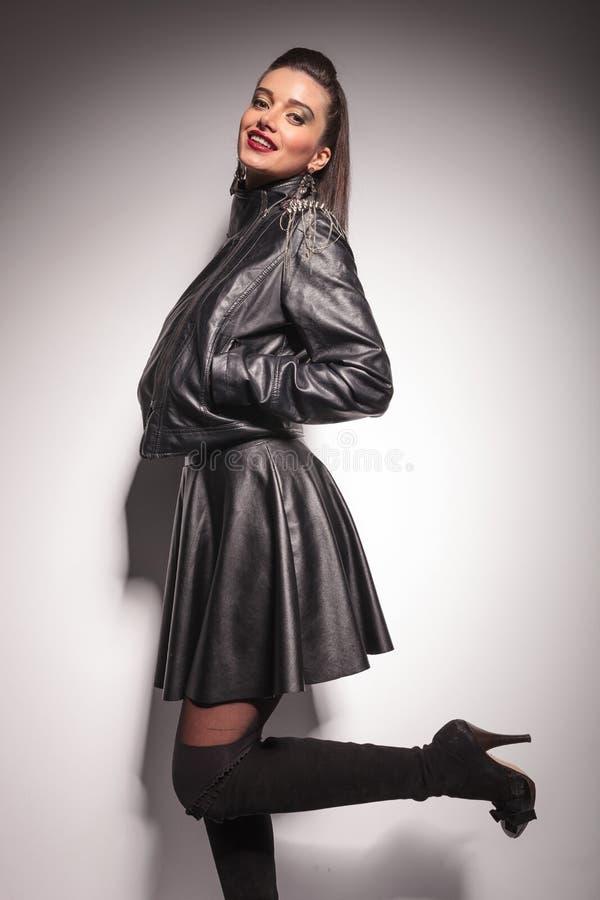 Усмехаясь женщина моды держа ее руки в карманн стоковые изображения